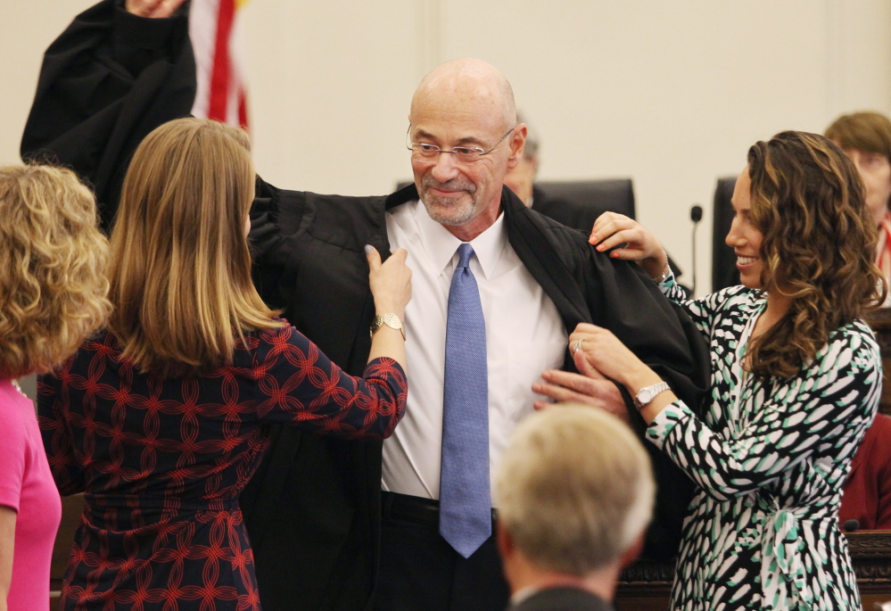 U.S. District Judge Jon David Levy of Portland gets some help  putting on his new robes from his daughters, Rachel Levy, left, and Anna Prager, during a ceremony Friday in Portland, where he was formally sworn in to the federal bench.