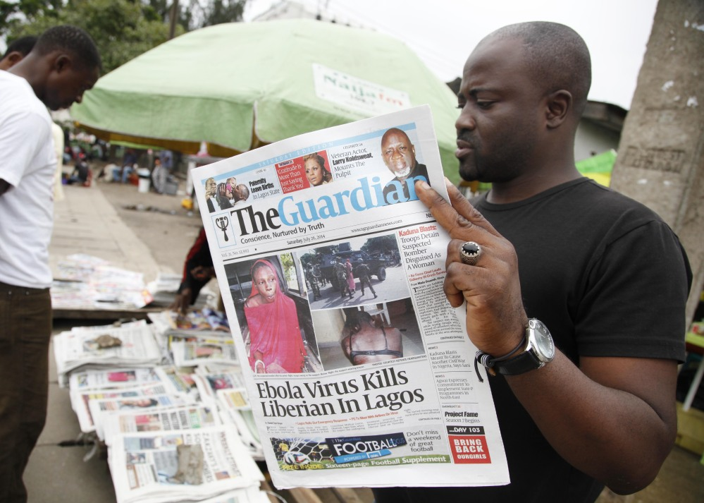 A man in Lagos, Nigeria, reads a local newspaper bearing a headline Saturday about the Ebola-caused death of a Liberian government worker who flew to Lagos from Togo.