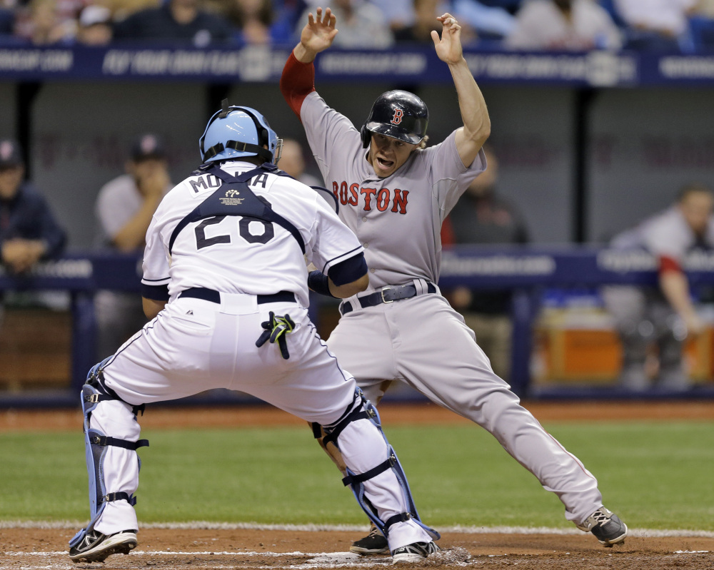 Boston's Brock Holt tries to elude Tampa Bay catcher Jose Molina while attempting to score on a ground out by David Ortiz the third inning Saturday in St. Petersburg, Fla. Holt was tagged out.