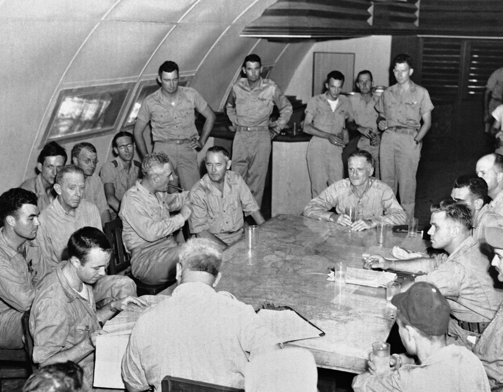 The crew of the Enola Gay is debriefed in Tinian, Northern Mariana Islands on Aug. 6, 1945 after returning from their atomic bombing mission over Hiroshima, Japan. At foreground left, seated at the corner of the table, is Capt. Theodore VanKirk, navigator.