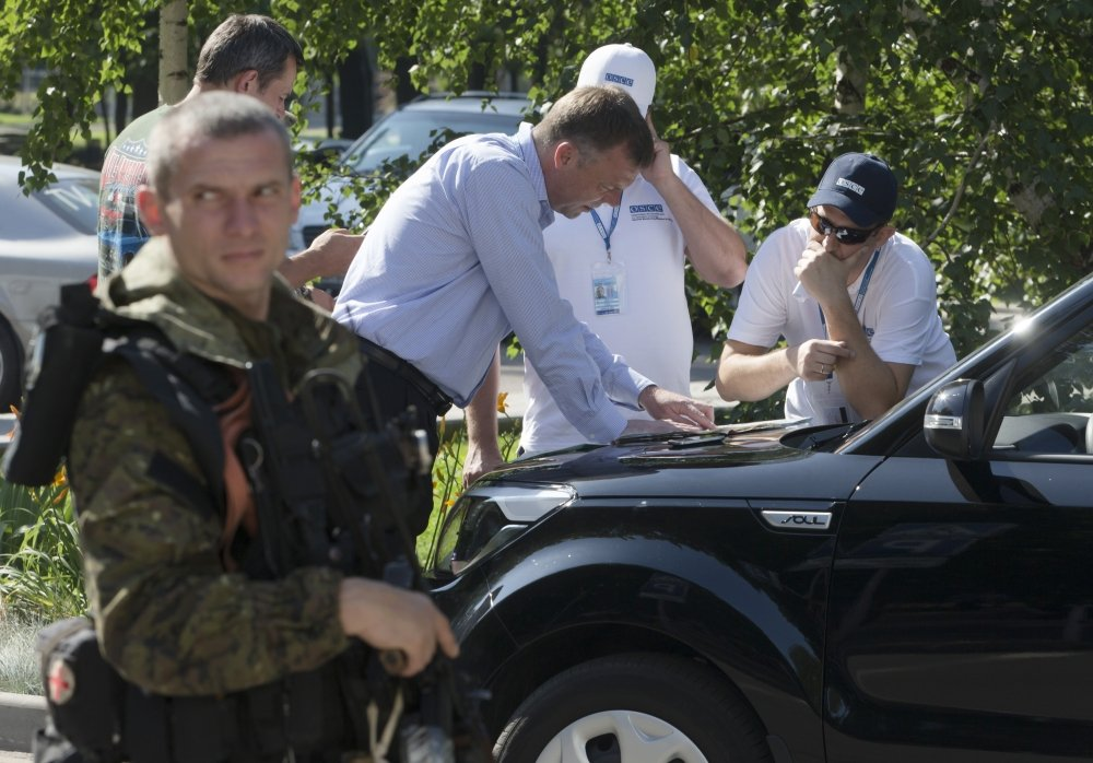 Alexander Hug, deputy head of the OSCE mission to Ukraine, center, and his colleagues examine a map as they discuss the situation around the site of the crashed Malaysia Airlines Flight 17, in the city of Donetsk, eastern Ukraine Wednesday.