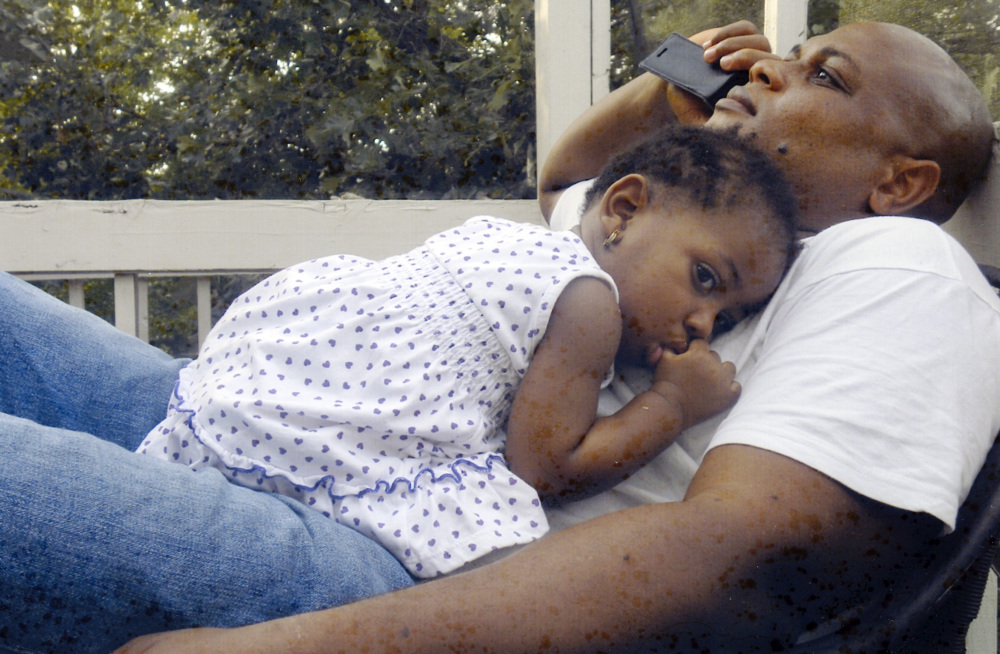 In this undated family photo, Patrick Sawyer is shown with his daughter Ava at their home in Coon Rapids. Sawyer  died from Ebola after traveling from his native Liberia to Nigeria. The Associated Press
