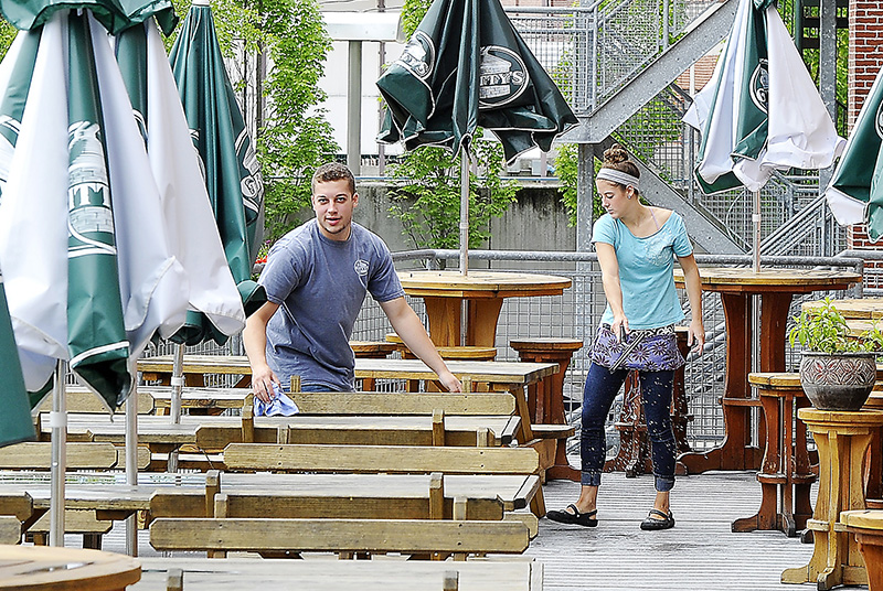 Josh Poulin and Jaclyn Masters, both servers for Griity McDuffs in Lewiston, sweegee and wipe the water from outdoor tables full of last nights rain from the passing storm before they open for the holiday weekend. Gordon Chibroski/Staff Photographer