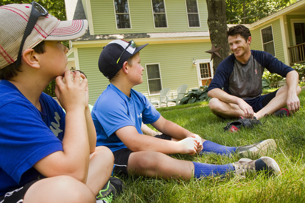 Cal Hodgdon and Camden Charron talk with McCarthy  in front of the Charron family's Falmouth home.