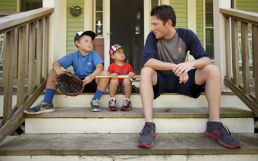 Camden and Jackson Charron,  age 9 and 4, sit on the front steps and talk baseball with Portland Sea Dogs pitcher Michael McCarthy, who lives with the Charron Family in their Falmouth home while the team is in Portland.