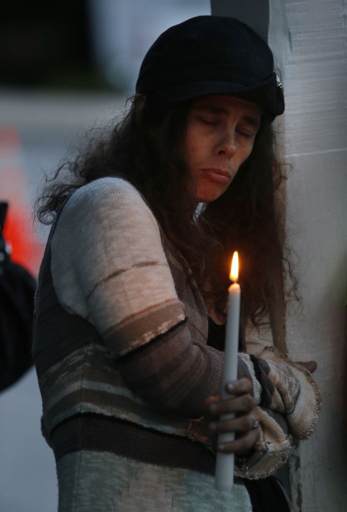 Kristi Harkins holds a candle and observes a moment of silence during Tuesday night's vigil for the Smith family in Saco.