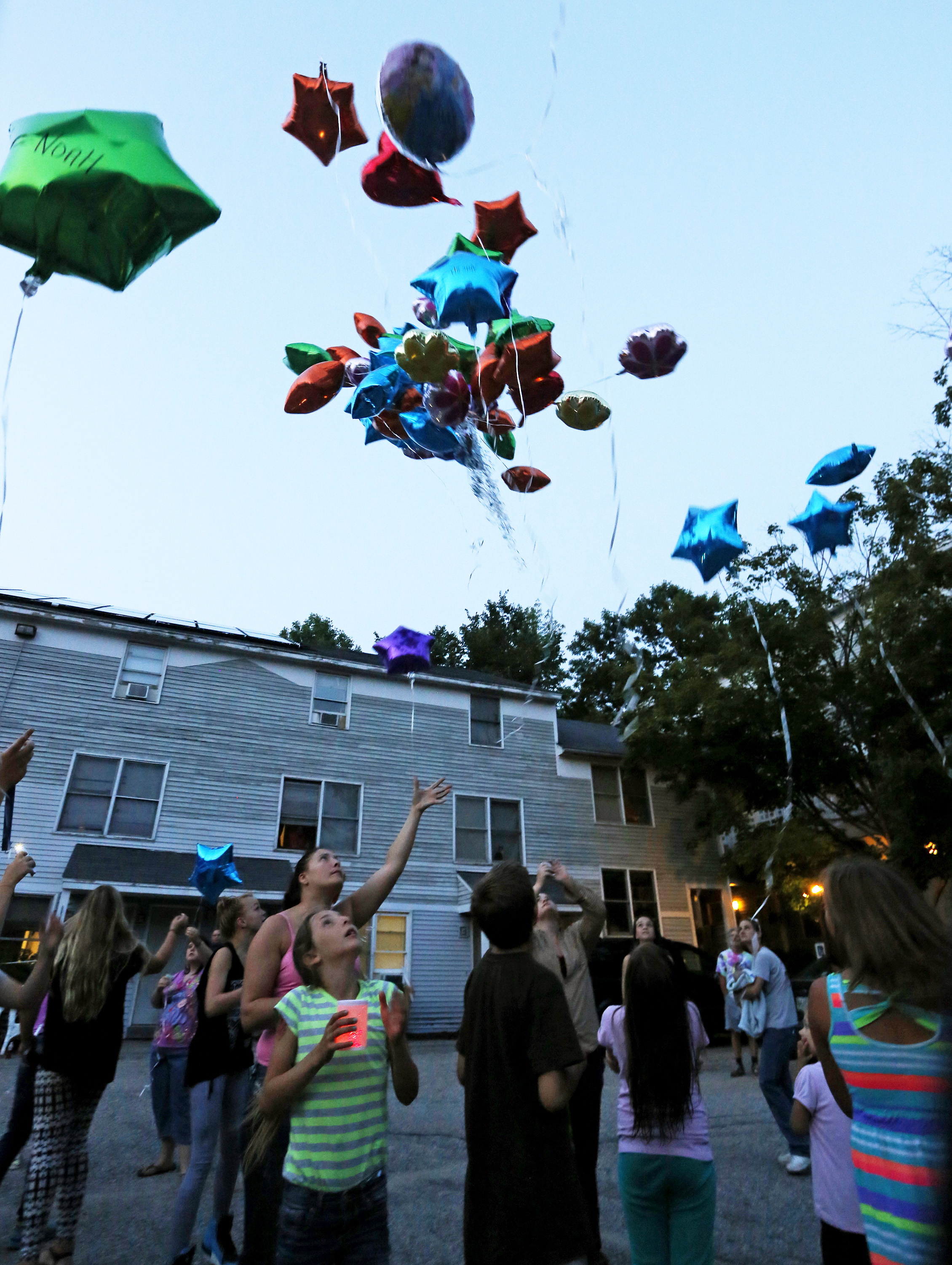 Residents of the RiverView apartments let balloons go, with messages written on them, during a vigil held for the Smith family Tuesday night.