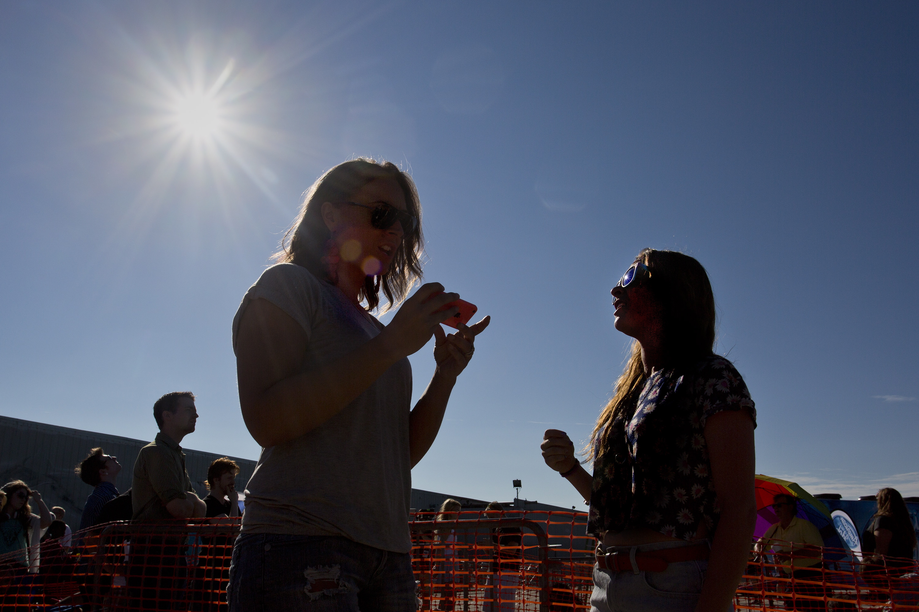 Matte Cardelli, 28, of New Auburn, uses her phone to look up song lyrics and she and her friend, Danielle Doucette, 23, of Berwick, at right, wait in line to audition for American Idol.