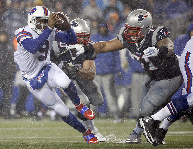 Buffalo Bills quarterback Thad Lewis (9) scrambles away from New England Patriots defensive tackle Sealver Siliga (71), The Associated Press