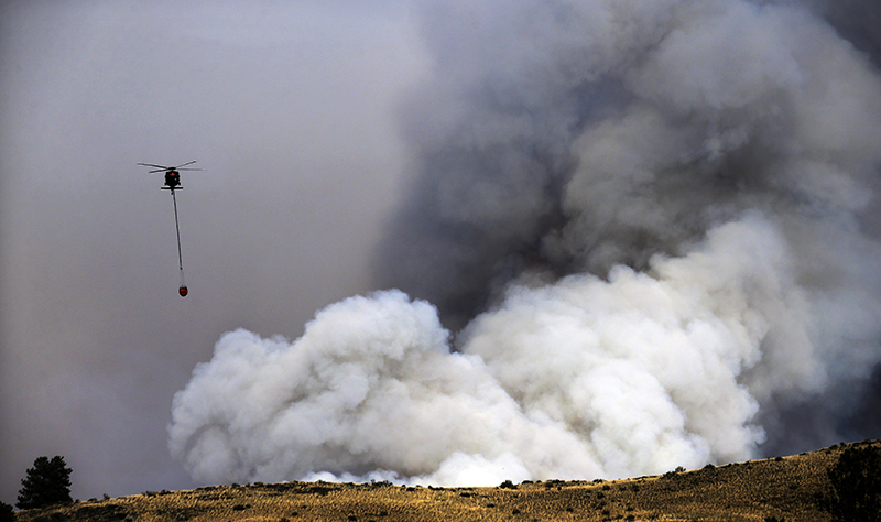 A helicopter preparing to drop water is dwarfed by a billowing cloud of smoke from a wildfire Friday, July 18. The Associated Press