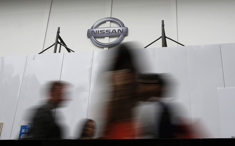 People walk past a wall set up in front of Nissan's showroom under renovation in Tokyo, Monday, May 12, 2014. The Associated Press