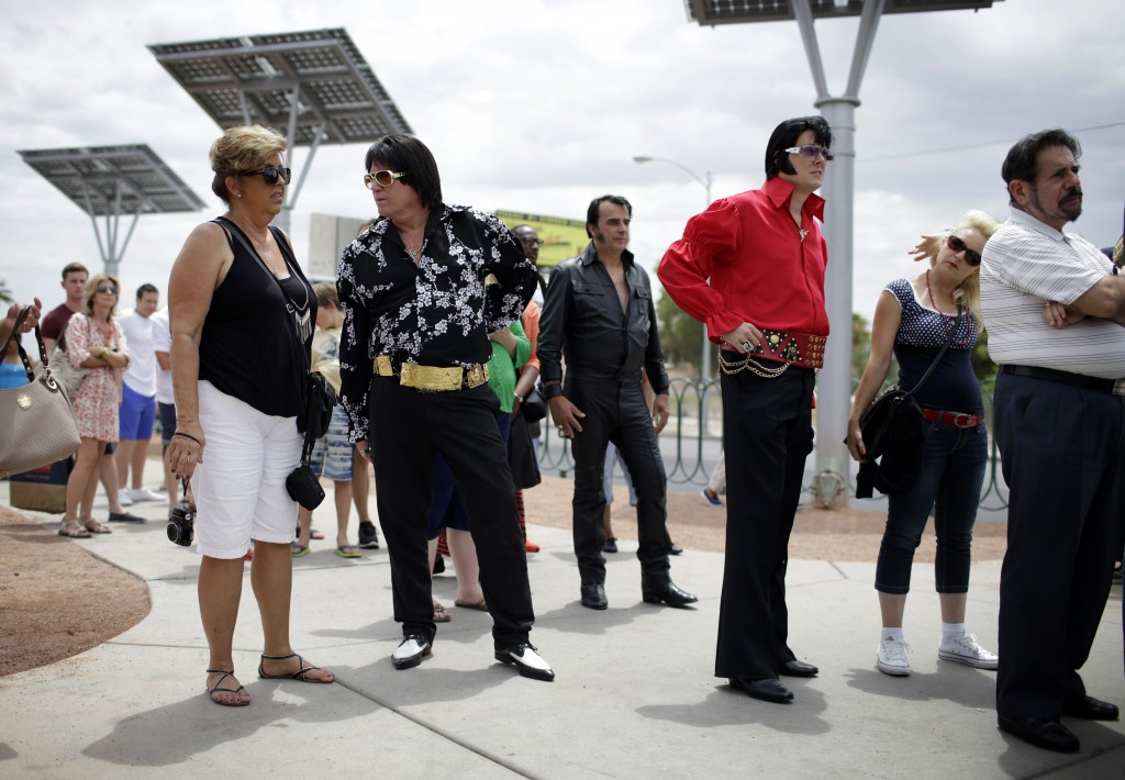"Elvis tribute artists participating in the Las Vegas Elvis Festival wait in line to take pictures in front of the ""Welcome to Las Vegas"" sign in Las Vegas. Several of the tribute artists took a bus tour around Las Vegas during the convention."
