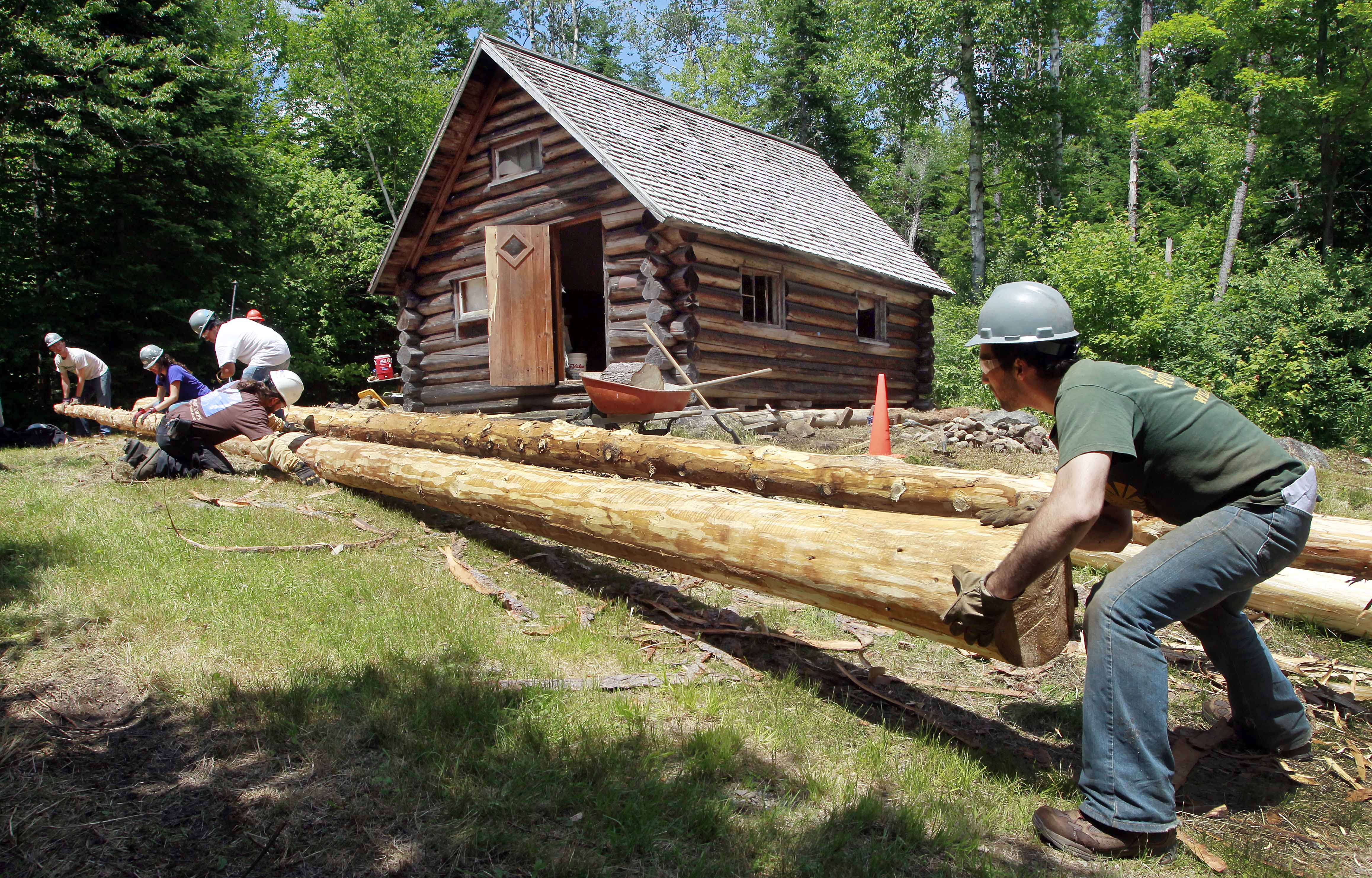 Volunteer Alex Gunn, right, helps roll a fresh cut red spruce with crews as they work to restore the Fabyan Guard Station in the New Hampshire White Mountain National Forest  in Carroll, N.H., on July 9.