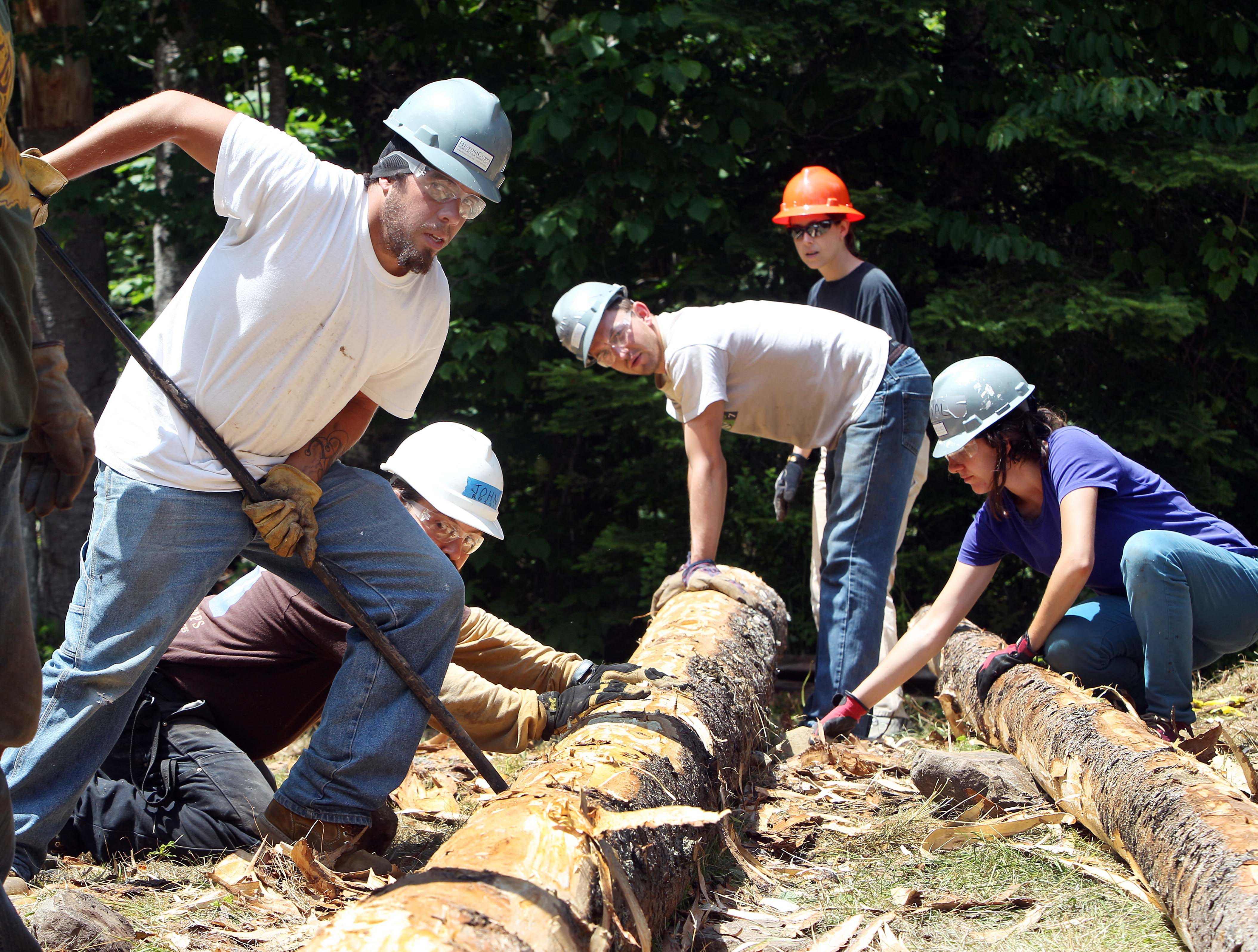 Christopher Ledoux, left, helps roll a freshly cut red spruce with crews as they work to restore the Fabyan Guard Station in the New Hampshire White Mountain National Forest, in Carroll, N.H., on  July 9.