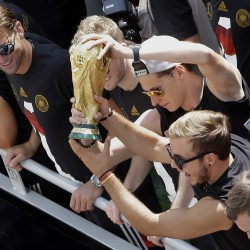 Soccer players Mario Goetze, right, and Julian Draxler , center, hold the trophy while goalie Roman Weidenfeller , left, looks on, as Germany's World Cup-winning team returned home from Brazil to celebrate the country's fourth title.