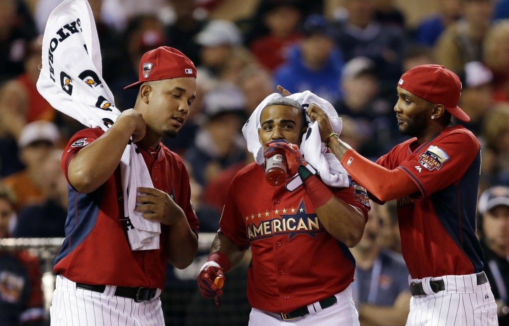 Yoenis Cespedes of the Oakland Athletics, center, gets some attention from teammates between pitches in the Home Run Derby on Monday in Minneapolis. Cespedes went on to win.