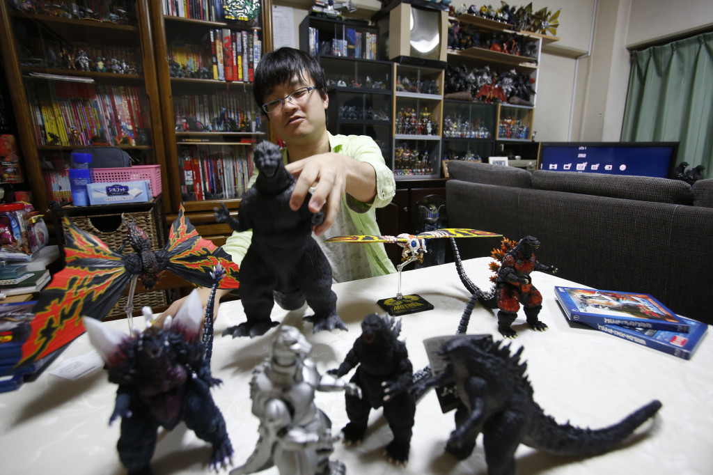 """Takeshi Maruyama, 28, picks up a model of the first Godzilla, shown with other items in his collection at his apartment in Yokohama, near Tokyo. """""""