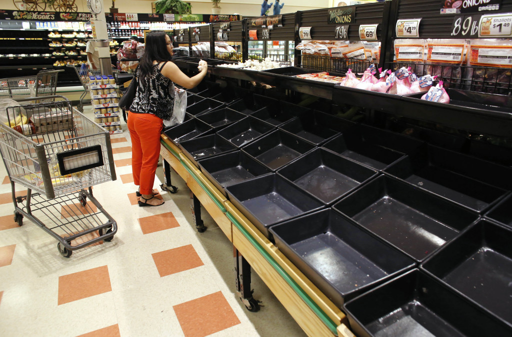 A shopper examines produce near empty bins in a Market Basket grocery store, on Tuesday in Chelsea, Mass. The Associated Press