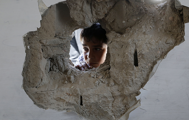 A boy looks through a hole on the wall made after an Israel strike at the Abu Hussein U.N. school in the Jebaliya refugee camp in the northern Gaza Strip on Wednesday. The Associated Press