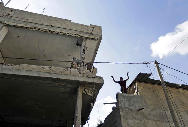 A member of the Keferna family cries upon his return to the family house. left, that was destroyed by Israeli strikes in Beit Hanoun, northern Gaza Strip, Saturday. The Associated Press