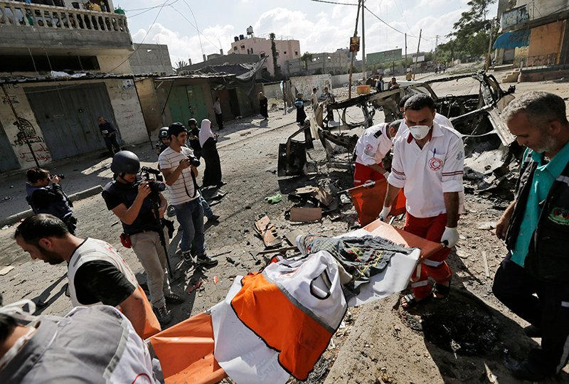 Palestinian medics carry the body of a colleague who was killed when the Red Crescent ambulance he was driving was destroyed by an Israeli strike in Beit Hanoun, northern Gaza Strip, Saturday. The Associated Press