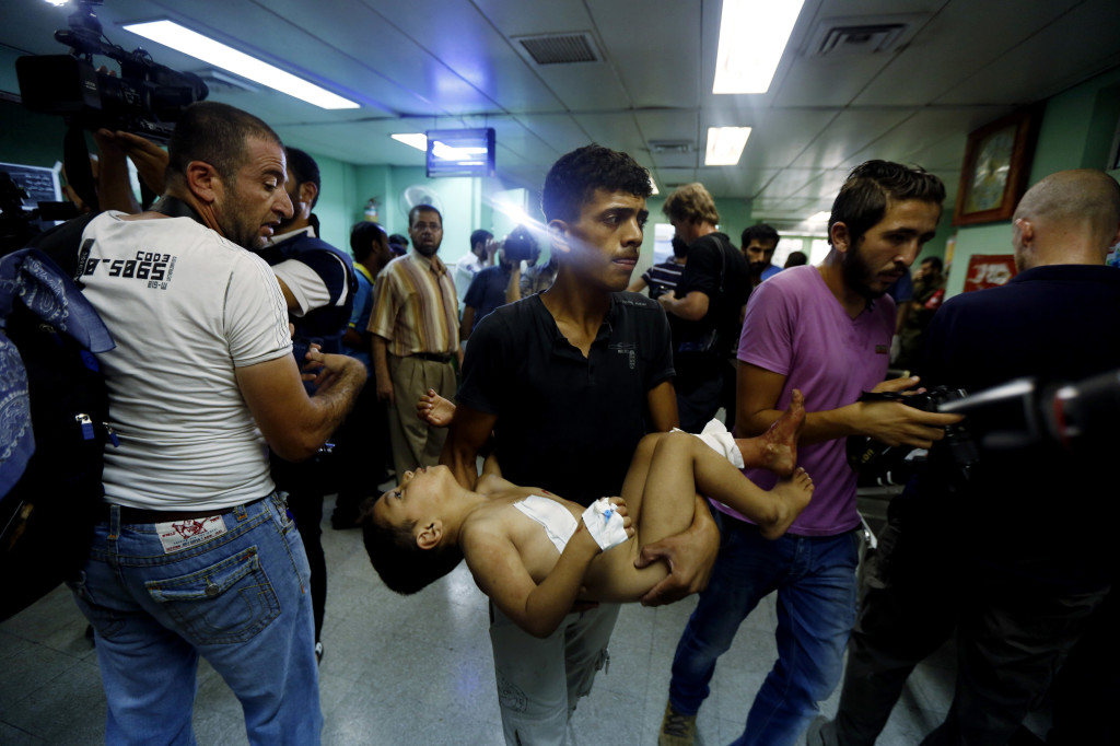 A Palestinian man carries a child, who was wounded in an Israeli strike on a U.N. school compound in the Gaza Strip, toward the emergency room of the Kamal Adwan hospital in Beit Lahiya, Thursday, The Associated Press