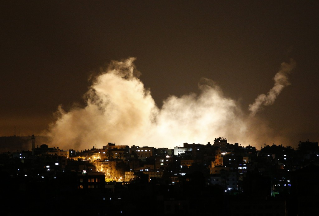 Smoke from flares rises in Gaza City on Thursday. Israel launched a large-scale ground offensive in the Gaza Strip and continued shelling into Friday morning, escalating a 10-day military operation to try to destroy Hamas' weapons arsenal, rocket firing abilities and tunnels under the Palestinian territory's border with Israel.
