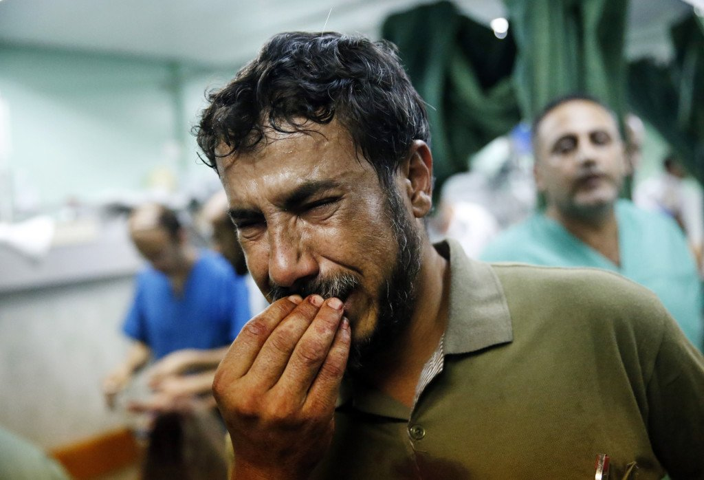 A Palestinian man cries after bringing a child who was wounded in an Israeli strike on a compound housing a U.N. school in Beit Hanoun to the emergency room of the Kamal Adwan hospital in Beit Lahiya on Thursday.  The Associated Press