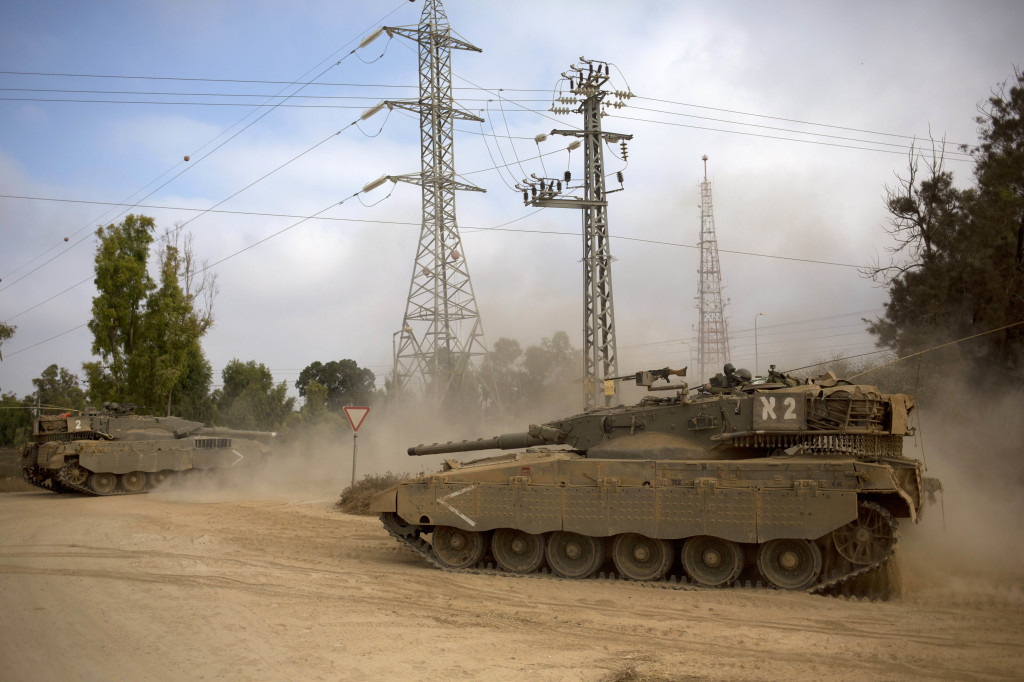 Israeli tanks move near the Israel and Gaza border in July 2014. The Associated Press