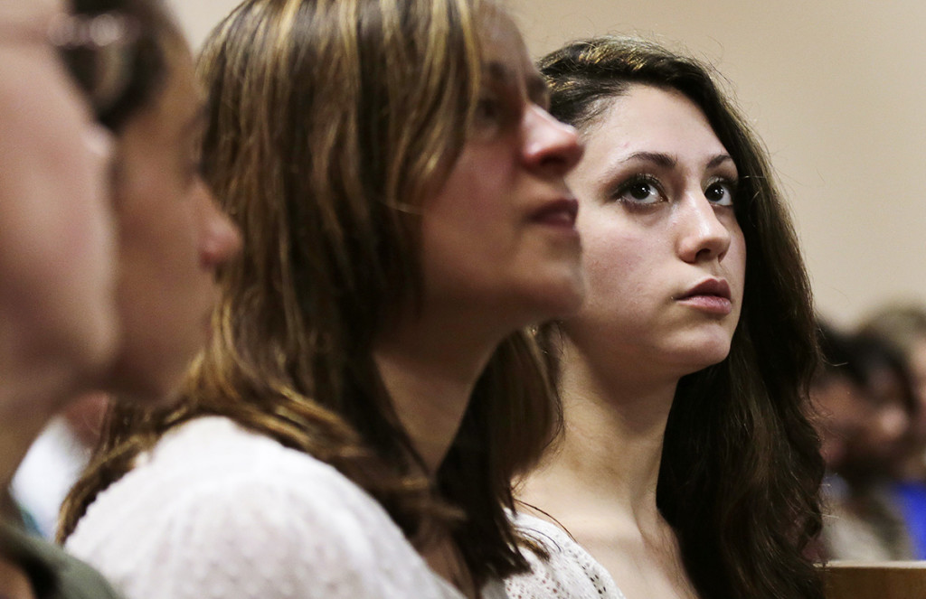 Abigail Hernandez, right, sits with family and friends as she listens to her mother Zenya Hernandez, center, talk with N.H. Senior Assistant Attorney General Jane Young, right, prior to the arraignment of Nathaniel Kibby, 34, of Gorham, N.H. at Conway District Court in Conway, N.H.