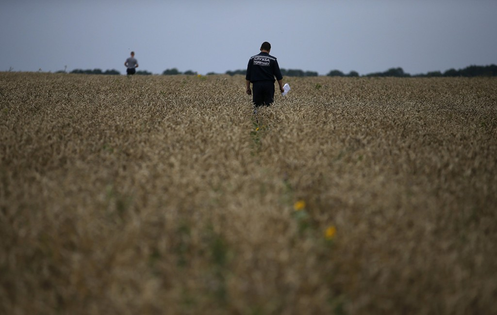 A member of the Ukrainian Emergency Ministry searches for bodies close to the site of Thursday's Malaysia Airlines Boeing 777 plane crash.