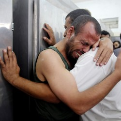 Palestinians mourn the death of their relatives, whom medics said were killed in Israeli shelling, at a hospital morgue in Rafah in the southern Gaza Strip July 21. Israeli tanks shelled militant targets in the Gaza Strip on Monday and a woman died in an air strike after the bloodiest day of a nearly two-week military offensive that showed no signs of abating, despite global calls for a truce.