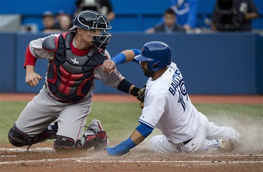 Blue Jays first baseman Jose Bautista slides past Red Sox catcher Christian Vazquez at home plate to score a run in the first inning Wednesday in Toronto. The Associated Press