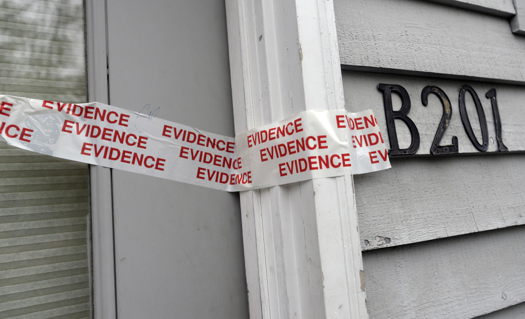 Evidence tape seals the door of the upstairs apartment where a family of five were found dead on Sunday at RiverView Apartments in Saco. Shawn Patrick Ouellette / Staff Photographer