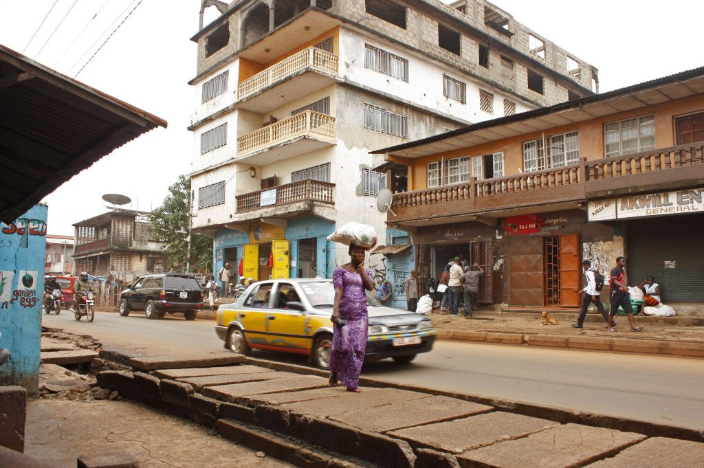 in this photo taken on  July 15, 2014,  a woman  walks near the Arwa clinic, center background,  that was closed after the clinic doctor got infected by the Ebola virus in the capital city of Freetown, Sierra Leone. The Associated Press