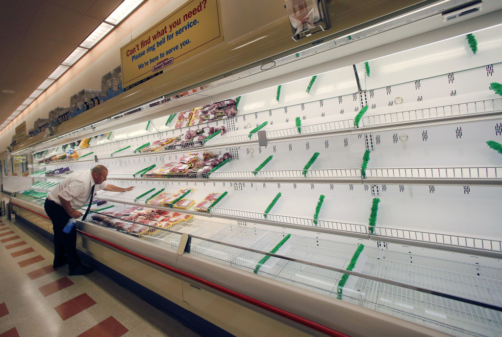 Meat manager Dave Fillebrown wipes down largely empty shelves last week at a Market Basket supermarket in Haverhill, Mass. The Associated Press