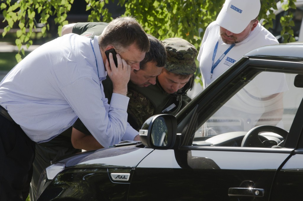 Alexander Hug, deputy head of the OSCE mission to Ukraine, left, his colleagues and a pro-Russian rebel, second from right, examine a map as they try to estimate security conditions around the site of the crashed Malaysia Airlines Flight 17 in eastern Ukraine Wednesday. The Associated Press