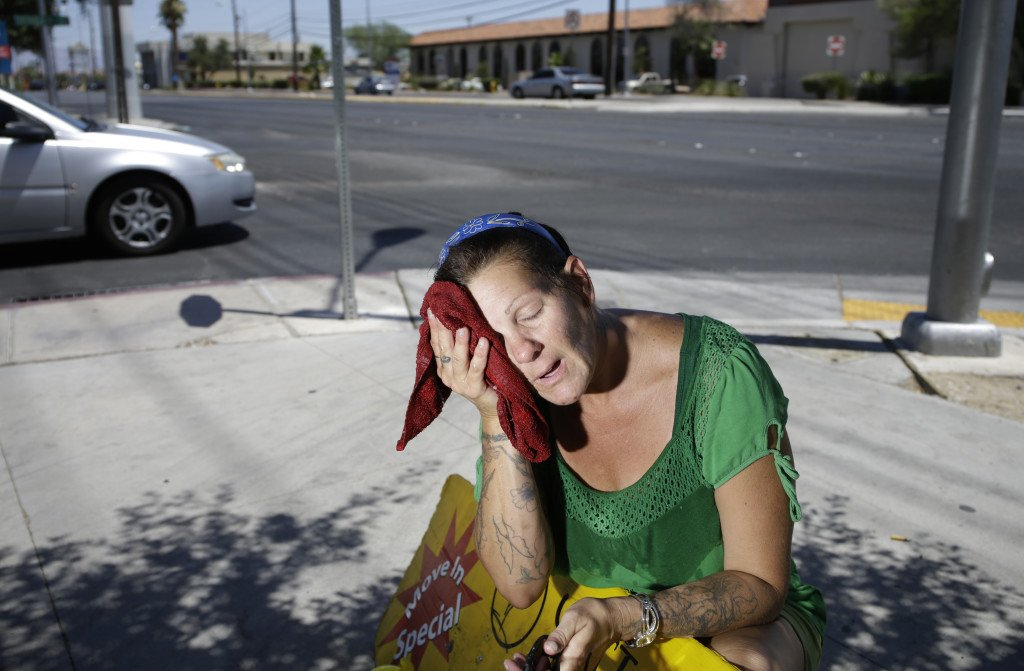 Amanda Ouellet wipes her face with a wet towel to cool off while working outside holding an advertising sign in Las Vegas in this n this July 1, 2014, photo. About 31 percent of the weather-related deaths in the U.S. between 2006 and 2010 were caused by heat, heat stroke or sun stroke, according to the CDC. The Associated Press