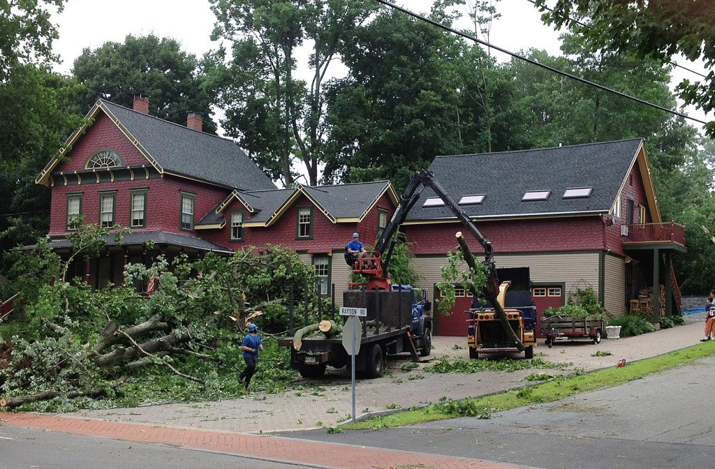 Crews work Wednesday morning to remove fallen trees at a home on Raydon Street in York.