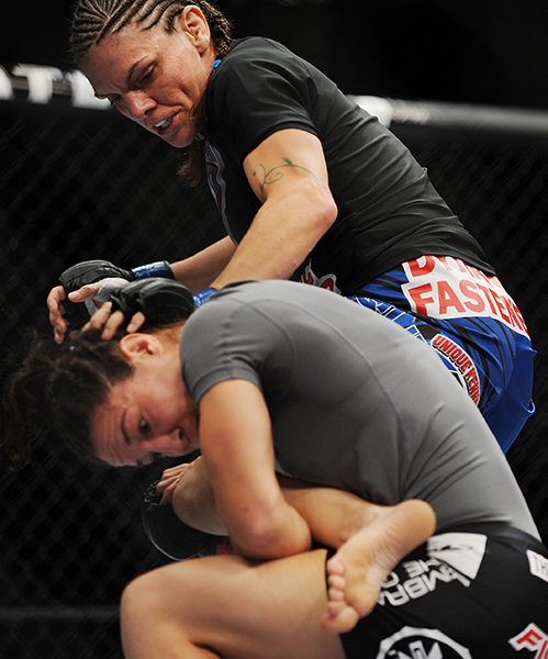 Sara McMann, red gloves and Lauren Murphy, blue gloves, square off in a flyweight bout at the Cross Insurance Center in Bangor on Saturday for Ultimate Fighting Championship fight night. Kevin Bennett/Special to the Telegram