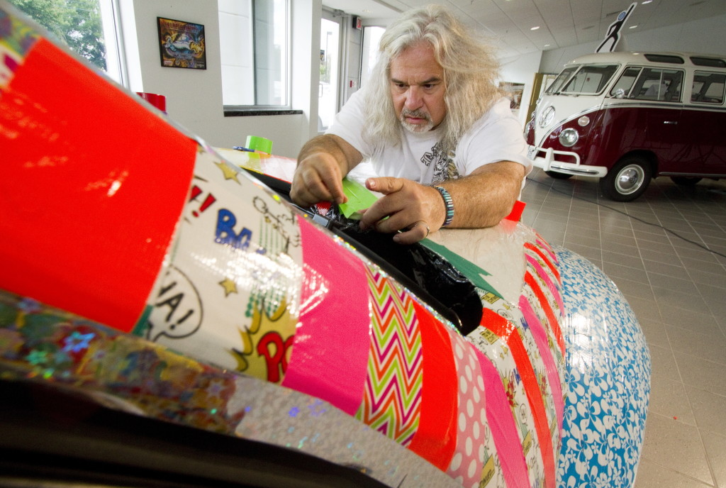 Digital artist Laurence Gartel works on his 37th Art Car at the Morong Falmouth dealership showroom Saturday. The completed car, a 2014 Volkswagen Beetle, was on display Sunday. Miami-based Gartel, considered a digital art pioneer, has worked with artists including Andy Warhol and Keith Haring and has displayed his work at major museums around the world. Photos by Carl D. Walsh/Staff Photographer