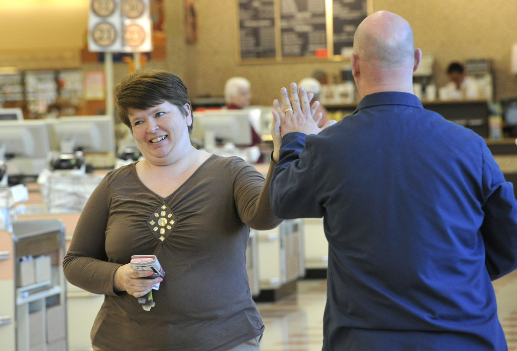 "Customer Wendy Newton of Lyman high-fives an employee at the Market Basket in Biddeford. Newton, who honored the boycott, said, ""I'm glad to be back."""