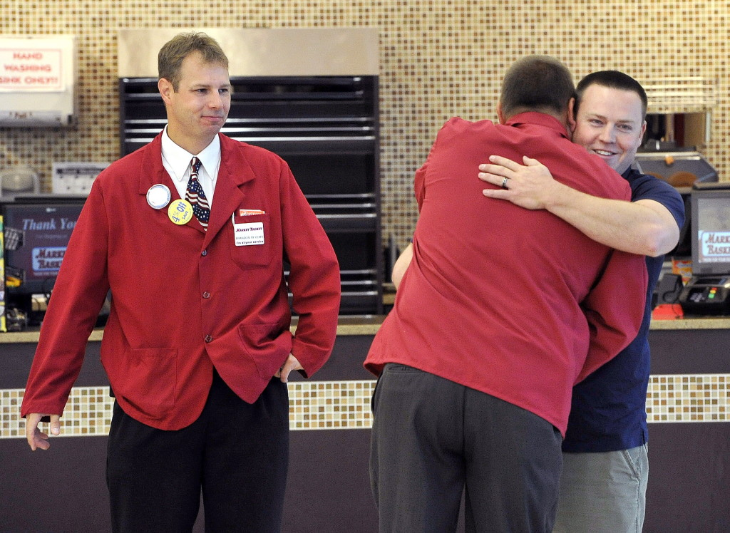 Pepperidge Farm vendor Robert Campbell, right, hugs employee Keith McGee as Brandon Gould watches at left, as workers celebrate getting back to work at the Market Basket in Biddeford on Thursday.