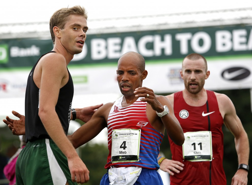 Will Geoghegan of Brunswick receives congratulations from Meb Keflezighi, this year's Boston Marathon winner, after Geoghegan finished the 17th annual TD Beach to Beacon 10k road race as the top Maine male on Saturday. Gabe Souza/Staff Photographer
