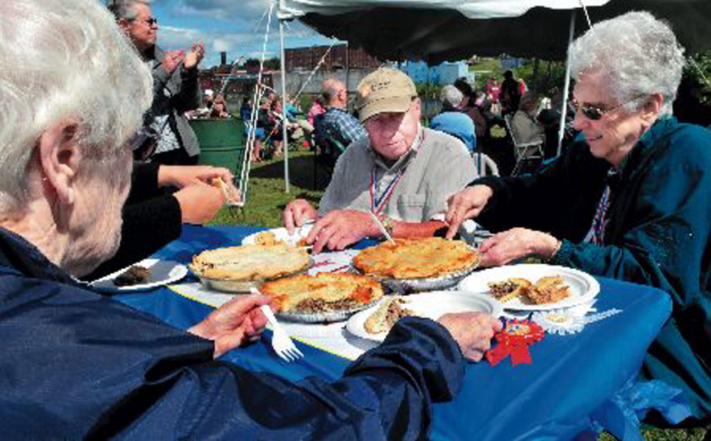 Judges sample tourtiere during a competition at the 2013 Franco-American Festival in Waterville.