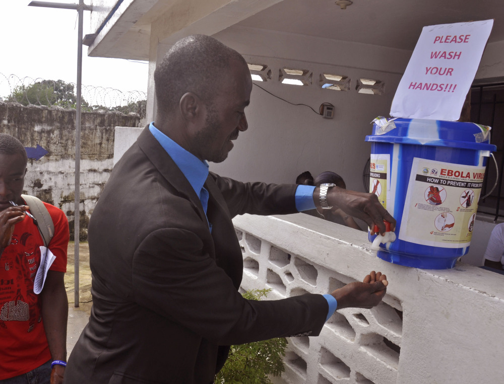 A man washes his hands before entering a public building as part of a drive to prevent the spread of the Ebola virus in the city of Monrovia, Liberia, on Thursday.