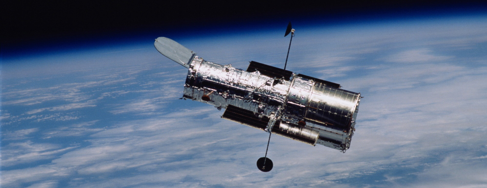 """The Hubble Space Telescope flies above the Earth. Scientists using it can see star formation 10.7 billion light years away through a newly discovered """"lensing"""" galaxy."""