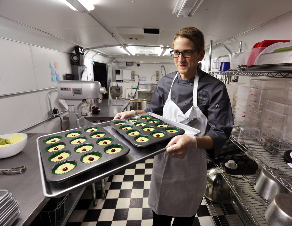 Chef Alex Tretter carries a tray of cannabis-infused peanut butter and jelly cups at Sweet Grass Kitchen, a Denver-based gourmet marijuana edibles bakery. Colorado  regulators seek to make it easier consumers to tell how much pot they are eating.