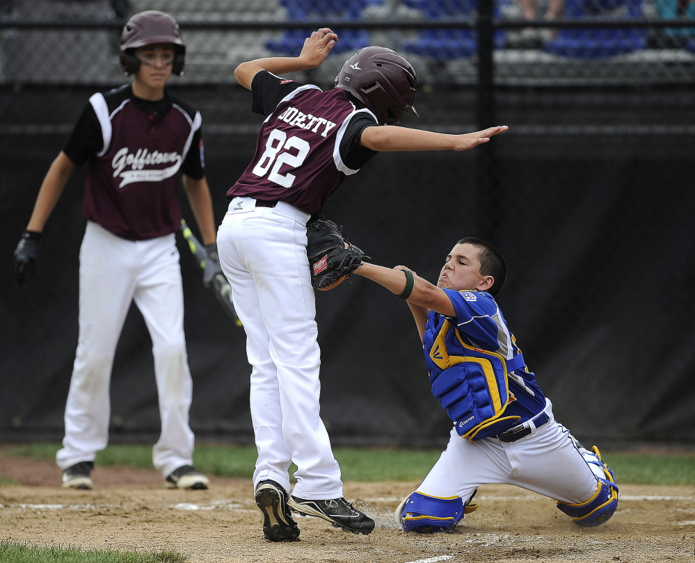 Falmouth catcher Francis Kiely tags out New Hampshire's Bobby Doherty at home plate despite Doherty's effort to avoid the tag.