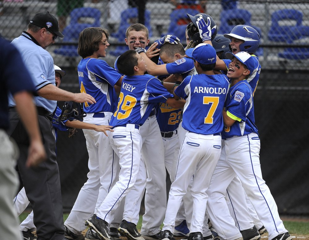 Alex Smith is mobbed by his teammate after his two-run homer with two outs in the bottom of the sixth inning Friday gave Falmouth a 3-2 win over Goffstown, New Hampshire, at the Little League New England Regional in Bristol, Connecticut.